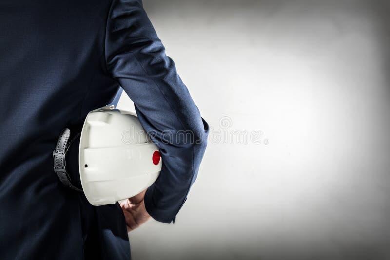Бизнесмен держа белый шлем безопасности стоковая фотография