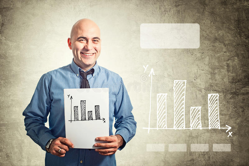 Бизнесмен держа бумажным с чертежом диаграммы в виде вертикальных полос стоковые изображения