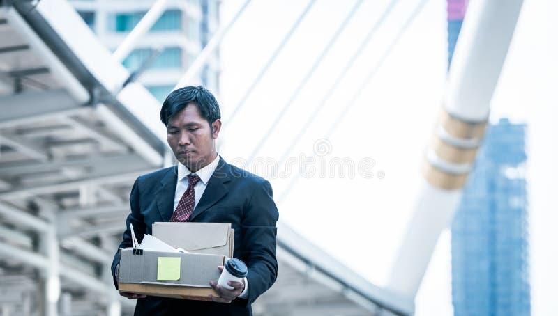 Бизнесмен держа держать картонную коробку при личные вещи покидая работа о стоковое фото rf