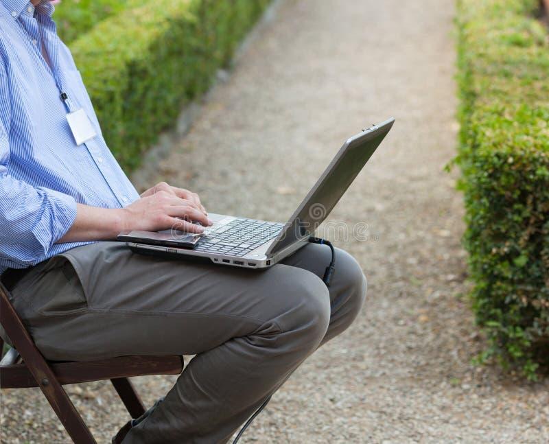 Бизнесмен держа компьтер-книжку на его коленях стоковые изображения rf