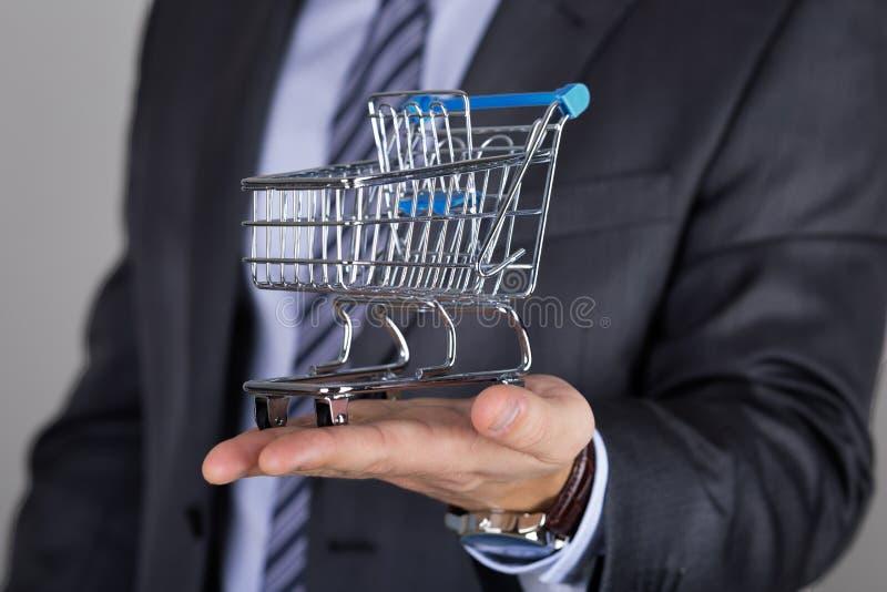 Бизнесмен держа магазинную тележкау стоковая фотография rf