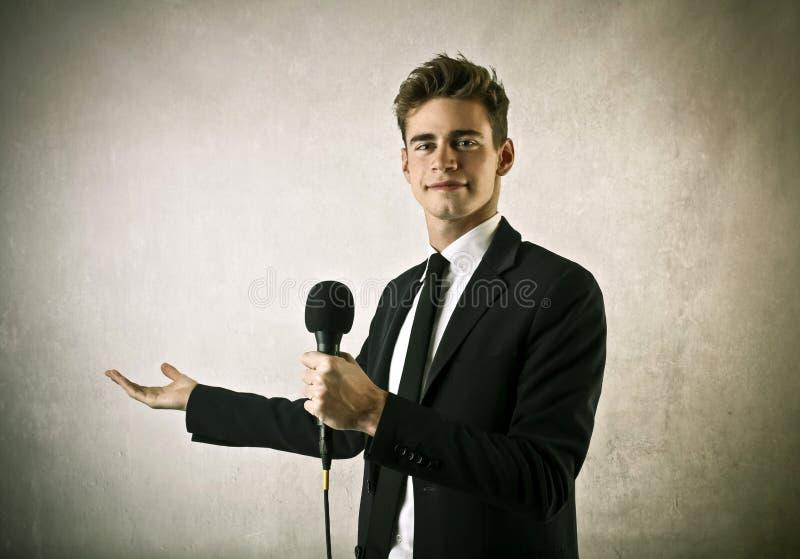 Бизнесмен держа микрофон стоковое изображение