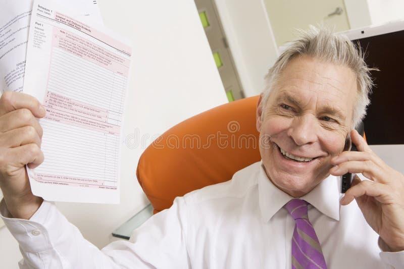 Бизнесмен держа налоговые формы стоковые фото