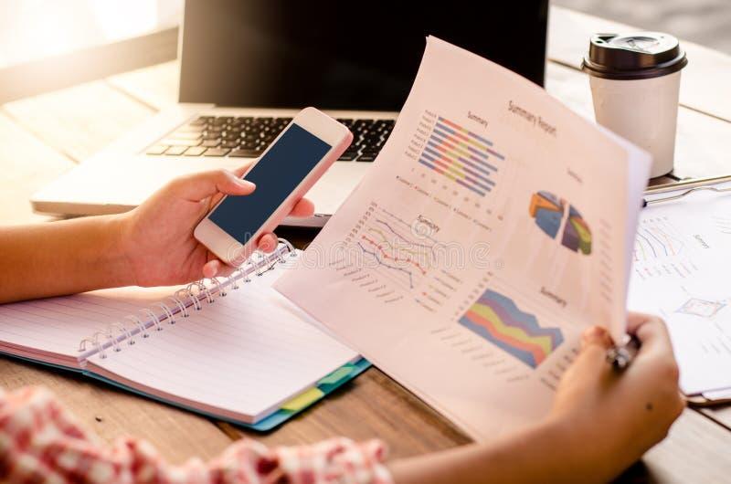 Бизнесмен держа обработку документов и умный телефон на таблице и анализируя диаграмму вклада работая в офисе Концепция работы де стоковое изображение