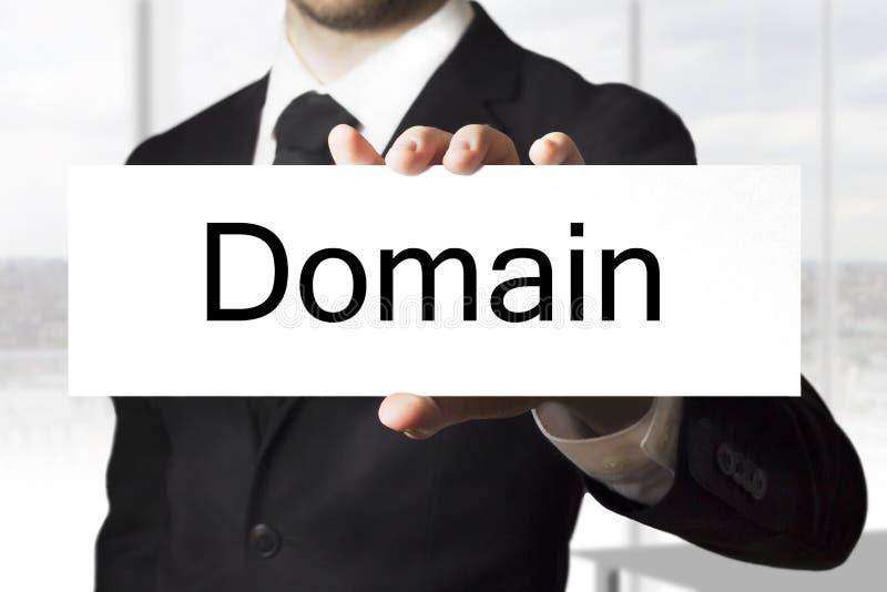 Бизнесмен держа домен знака стоковое фото