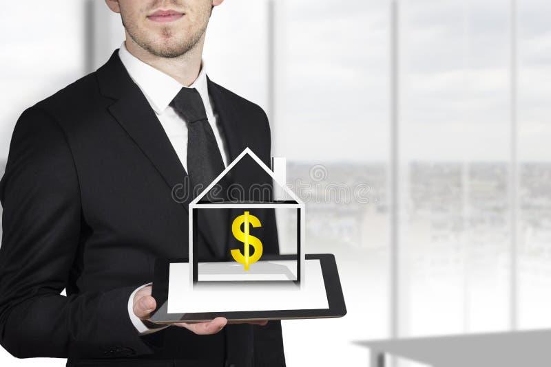 Бизнесмен держа дом доллара таблетки стоковые фото