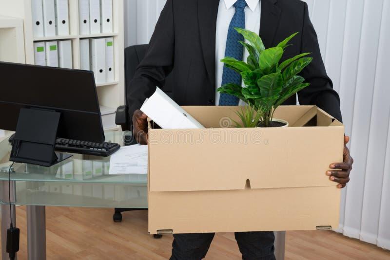 Бизнесмен держа папку и завод в картонной коробке стоковое изображение