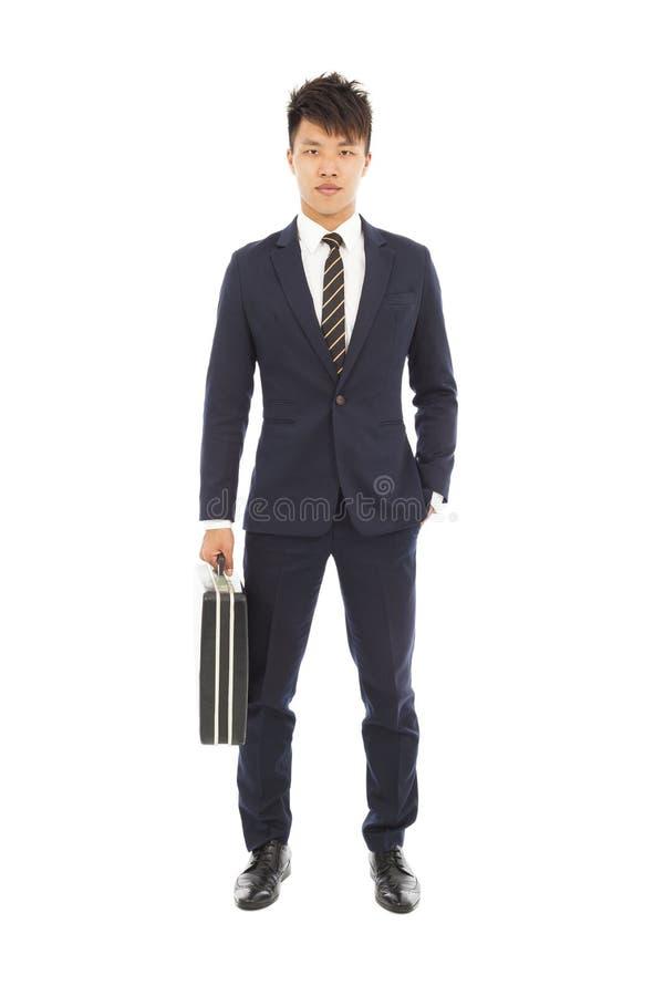 Бизнесмен держа портфель и руку в его карманн стоковое изображение