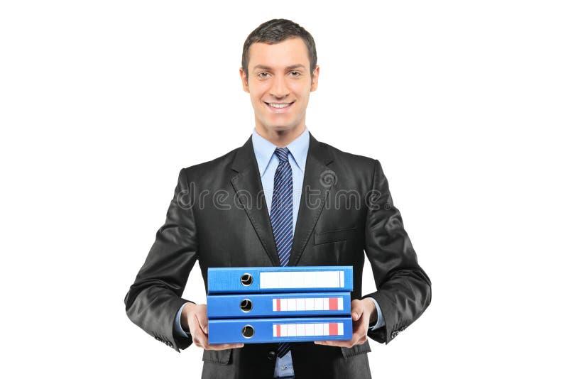 Бизнесмен держа пук папок стоковое изображение
