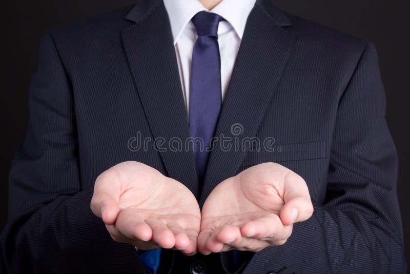 Бизнесмен держа руку представляя продукт стоковое фото rf