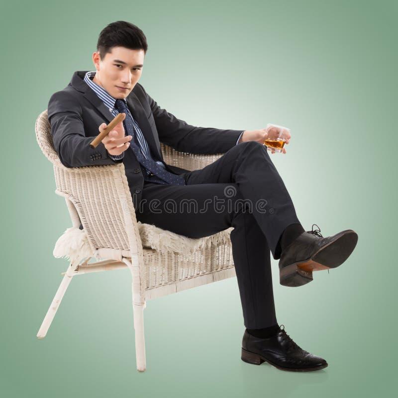 Бизнесмен держа сигару стоковое изображение rf