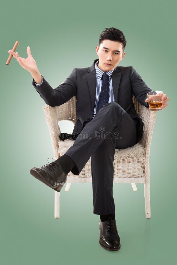 Бизнесмен держа сигару стоковая фотография