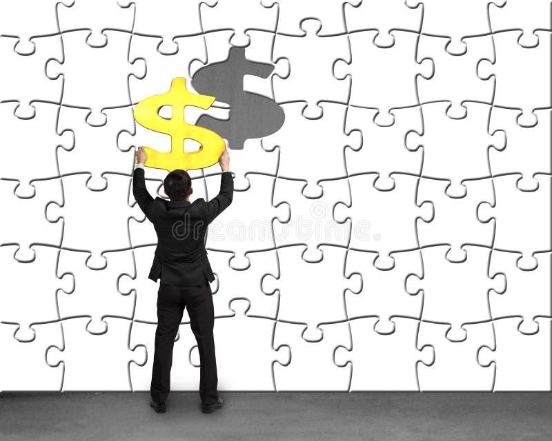 Бизнесмен держа символ денег собирая к головоломкам стену стоковое изображение