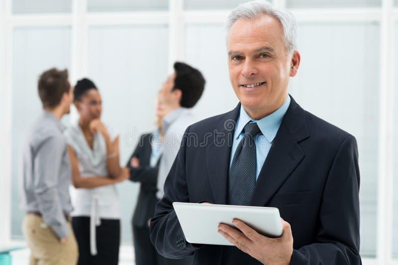 Бизнесмен держа таблетку цифров стоковое изображение