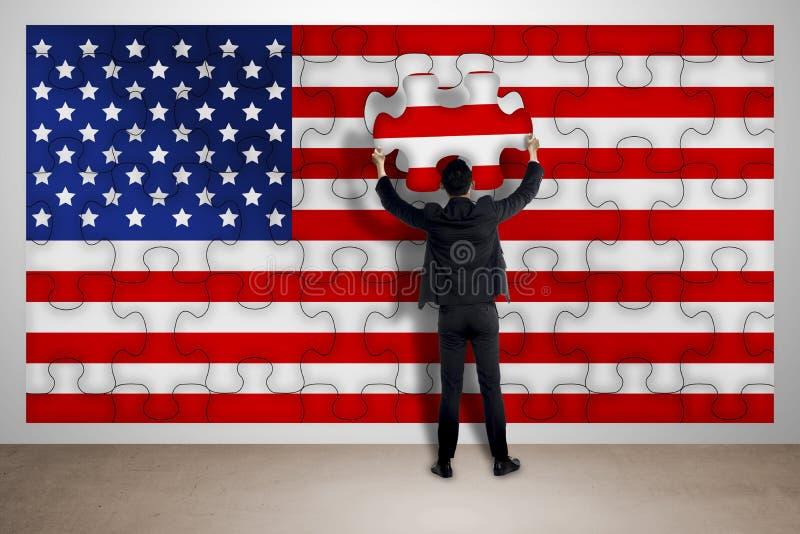 Бизнесмен держа часть головоломки, делая флаг США бесплатная иллюстрация