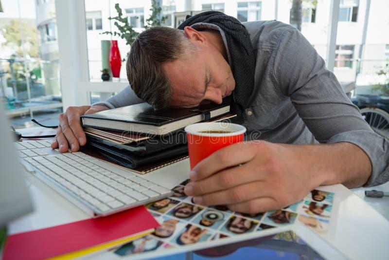 Бизнесмен держа чашку спать на файлах на столе стоковые фото
