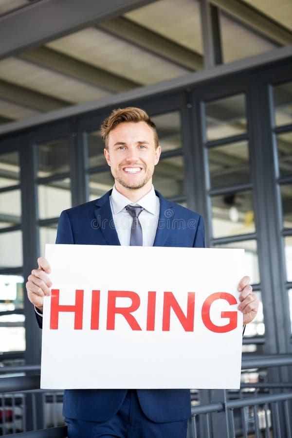 Бизнесмен держа шильдик рабочего места стоковая фотография rf