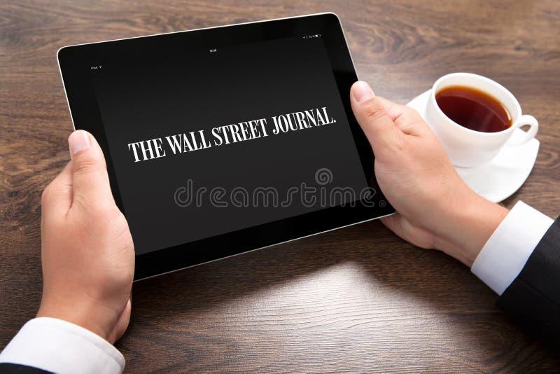 Бизнесмен держа ipad с Журналом Уоллом Стритом на экране стоковое изображение