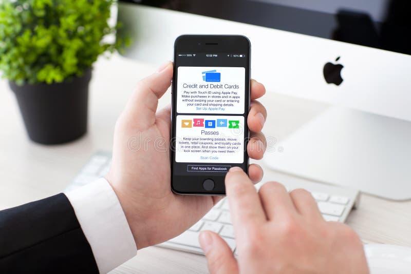 Бизнесмен держа iPhone 6 с оплатой и банковской книжкой на предъявителя Яблока стоковые фото