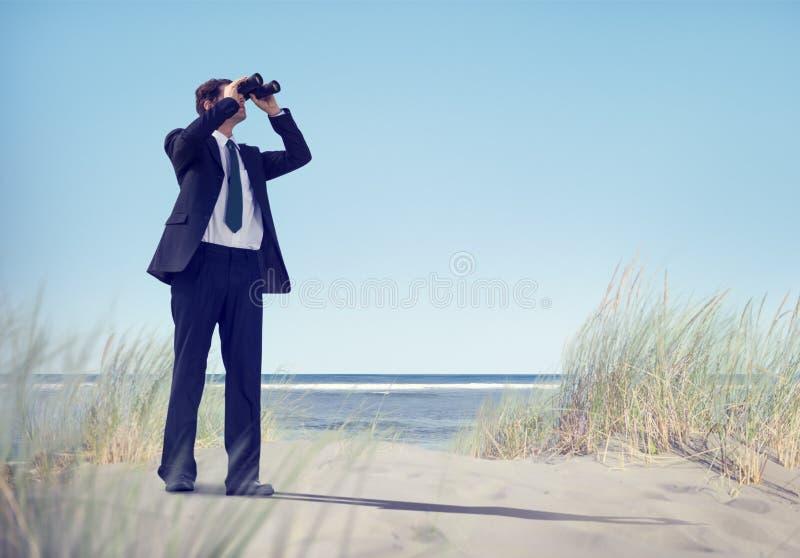 Бизнесмен держа Spyglass на пляже стоковое фото