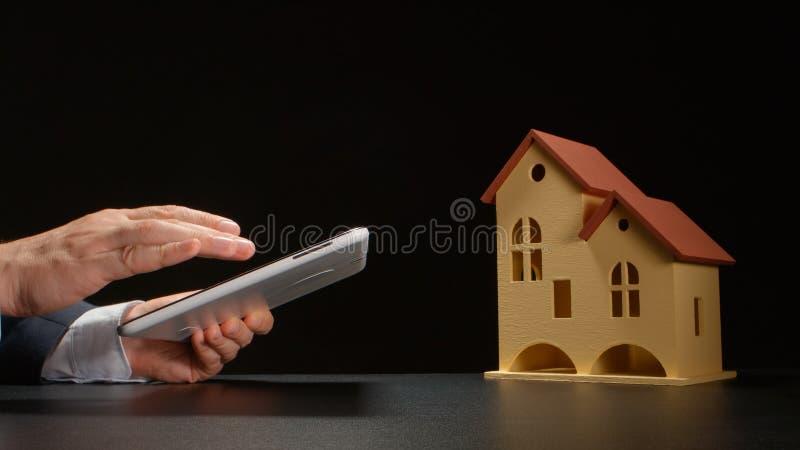 Бизнесмен держит ПК таблетки на руках около модели дома на конце таблицы вверх стоковые изображения