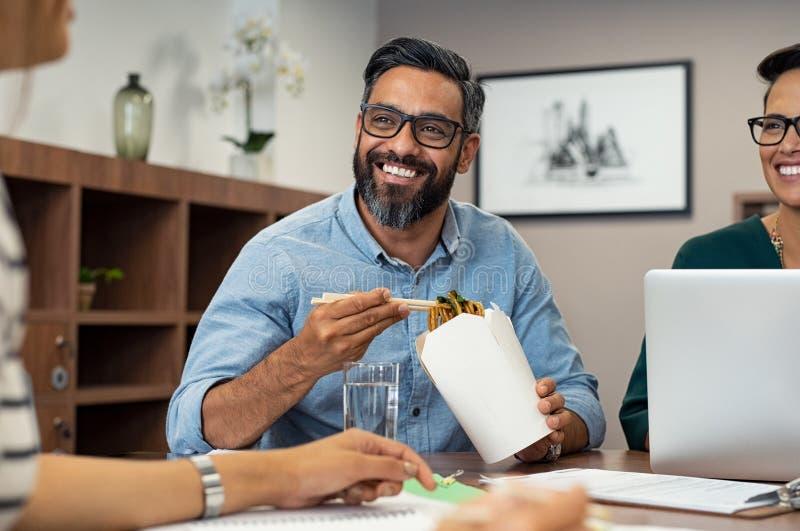 Бизнесмен есть лапши во время перерыва на ланч стоковое фото