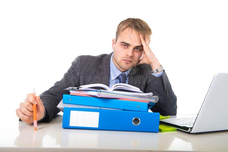 Бизнесмен детенышей перегружанный и сокрушанный в склонности стресса на отжатой папке офиса вымотанной и стоковые фотографии rf