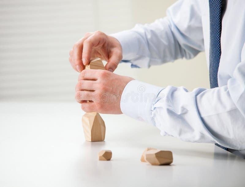 Бизнесмен делая башню из деревянных блоков стоковое изображение
