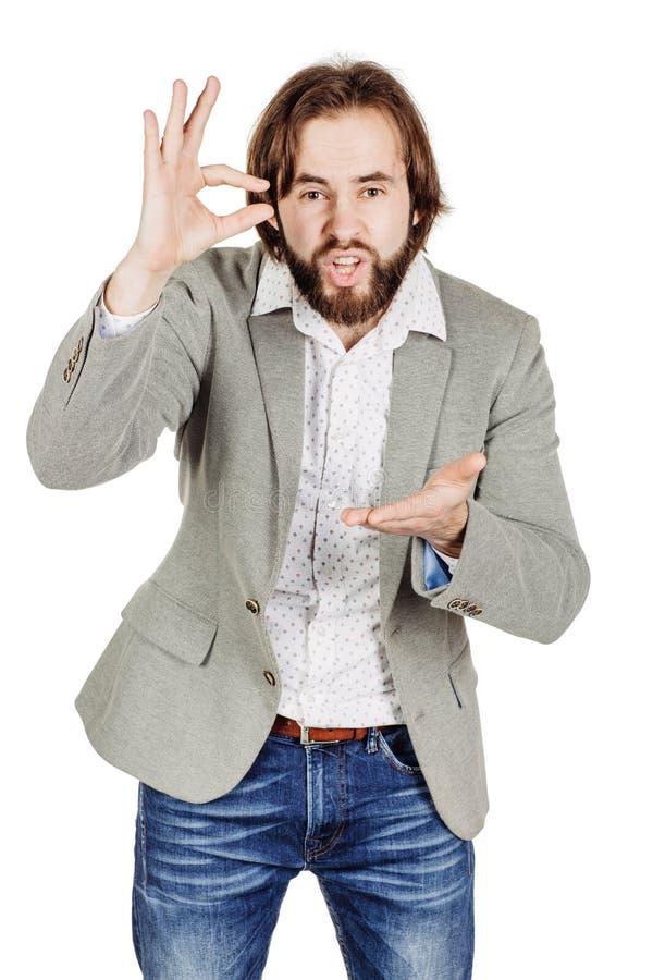 Бизнесмен делая его пальцами малый размер эмоции, уход за лицом стоковое фото