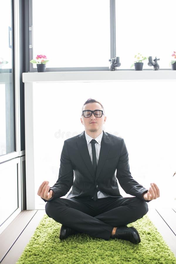 Бизнесмен делая йогу на зеленом цвете carpen в комнате отдыха офиса стоковое фото rf