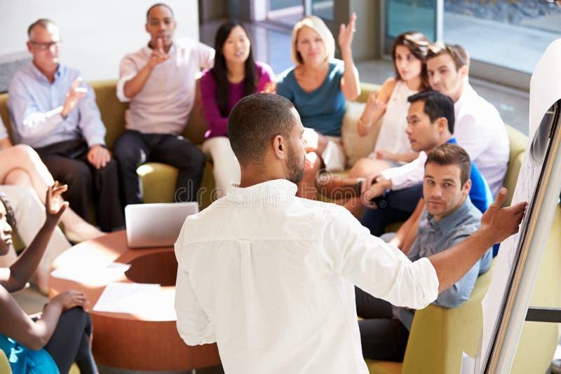 Бизнесмен делая представление к коллегам офиса стоковые изображения