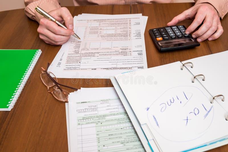 Бизнесмен заполняя вне налоговую форму 1040 стоковая фотография
