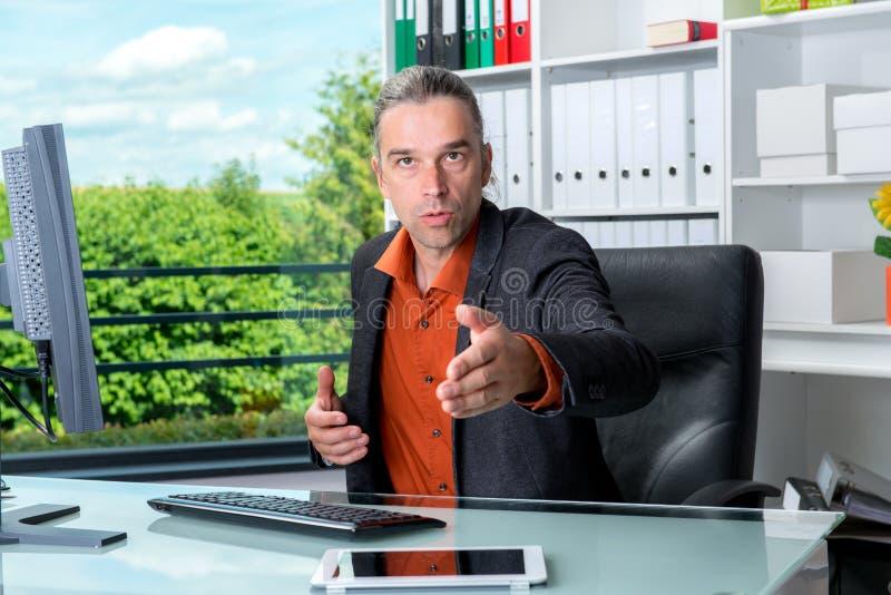 Бизнесмен за его столом приветствовал клиента стоковые фотографии rf