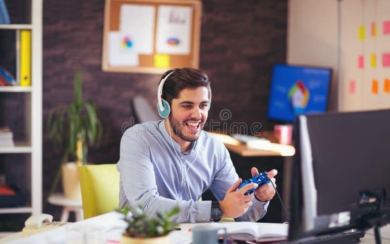Бизнесмен играя видеоигры в его офисе стоковые изображения