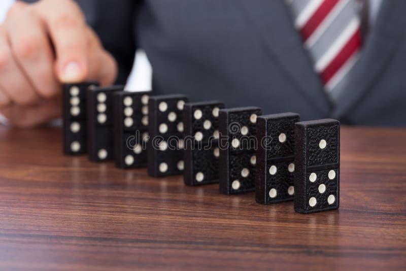 Бизнесмен играя домино на столе стоковое фото