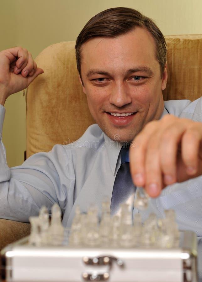 Бизнесмен играя шахмат в офисе стоковое фото rf