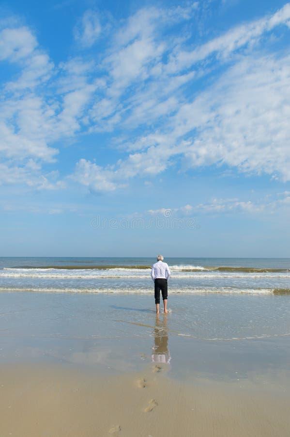Бизнесмен идя в море стоковые фото