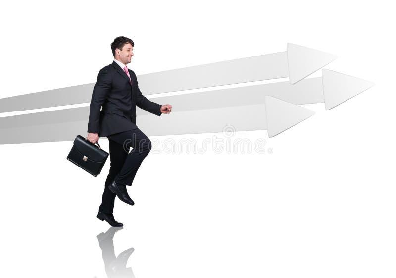 Бизнесмен идя около больших серых стрелок стоковое изображение