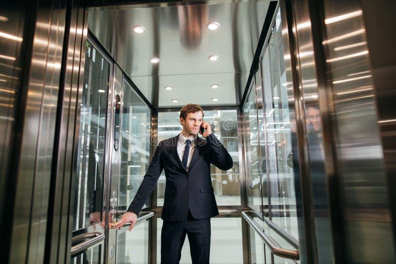 Бизнесмен идя пока говорящ на мобильном телефоне на его пути работать стоковое фото rf
