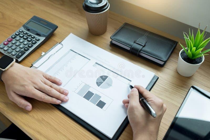 Бизнесмен идя через некоторую обработку документов и подписывая документ на столе в офисе стоковое фото rf