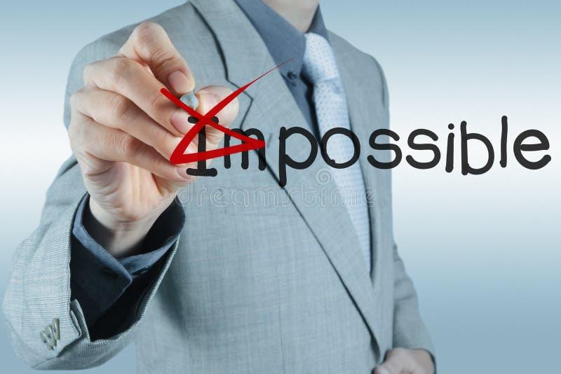 Бизнесмен изменяя слово невозможное в возможное стоковая фотография rf