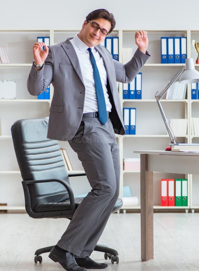 Бизнесмен имея потеху принимая перерыв в офисе на работу стоковое изображение