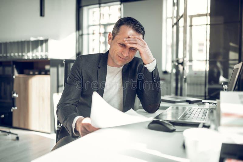 Бизнесмен имея слишком много усложнений работая на отчете стоковые фото