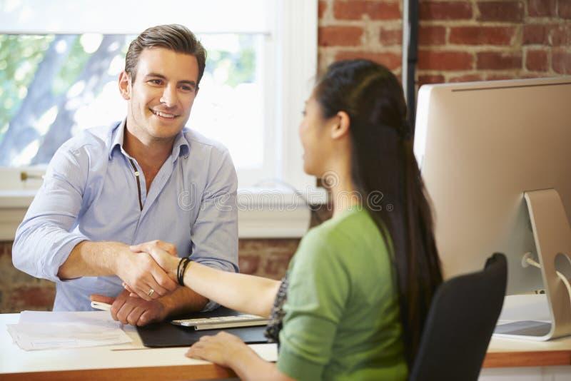 Бизнесмен интервьюируя женский соискателя в офисе стоковое фото rf