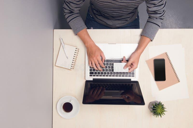 Бизнесмен использует карту и печатает на ноутбуке на таблице офиса r стоковые фото