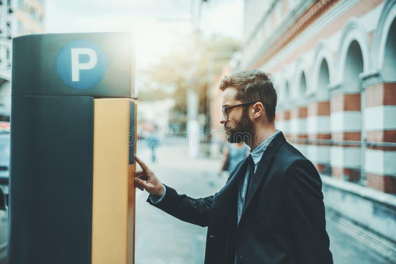 Бизнесмен используя автопарковочный счетчик outdoors стоковая фотография rf
