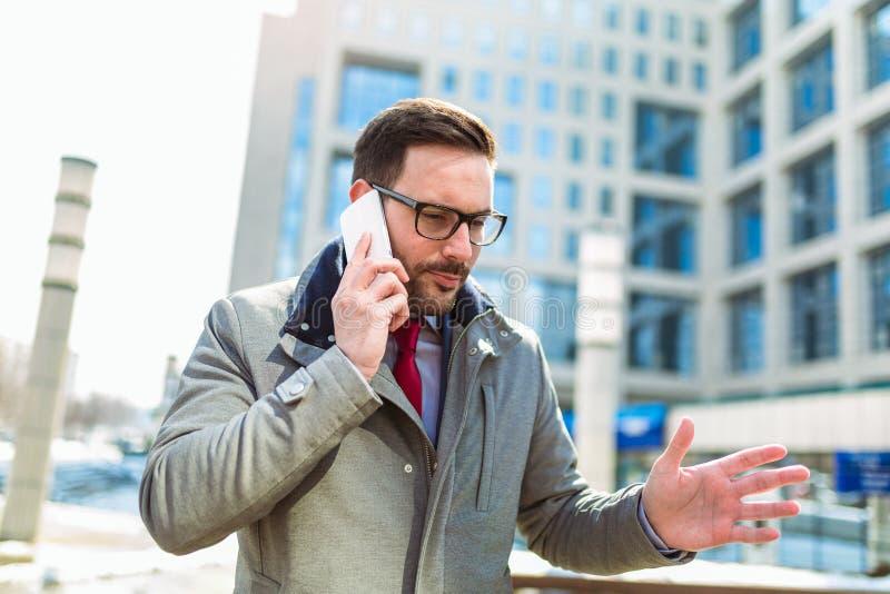 Бизнесмен используя мобильный телефон вне офисных зданий стоковые изображения rf