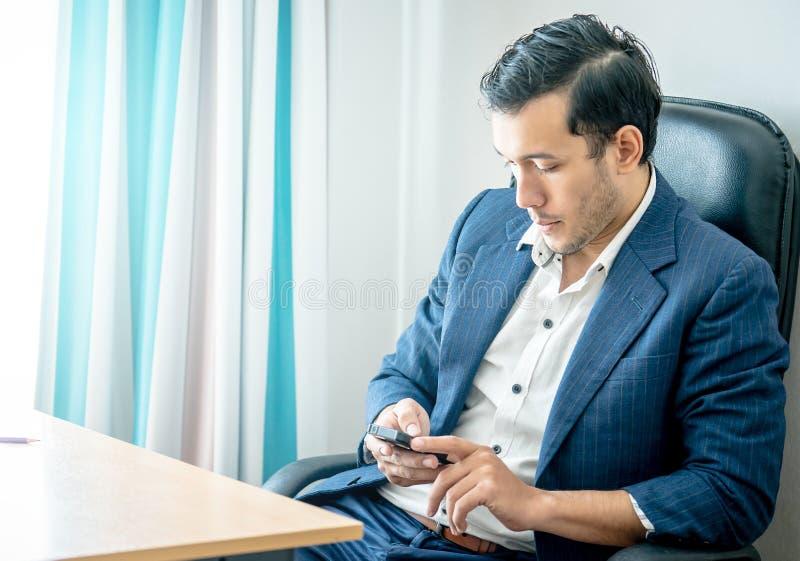Бизнесмен используя мобильный телефон в столе офиса стоковые изображения rf