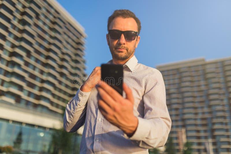 Бизнесмен используя мобильный телефон экрана касания outdoors стоковая фотография