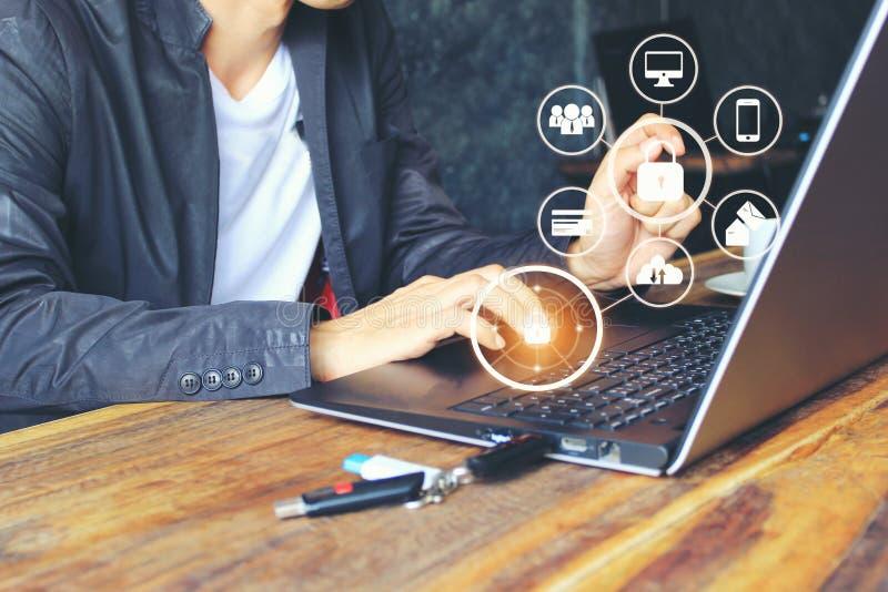 Бизнесмен используя ноутбук и руку держа мобильный умный телефон с hologram в домашнем офисе, GDPR безопасность кибер и стоковое изображение